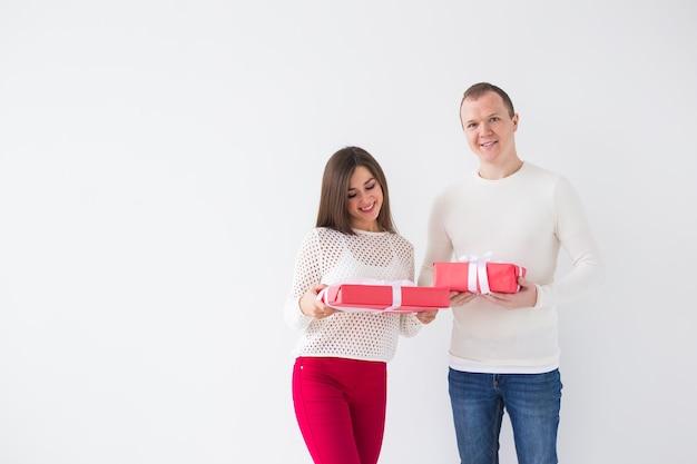 Kerstmis, feestdagen, valentijnsdag en verjaardag concept - gelukkige man en vrouw houden dozen met geschenken op witte achtergrond met kopieerruimte