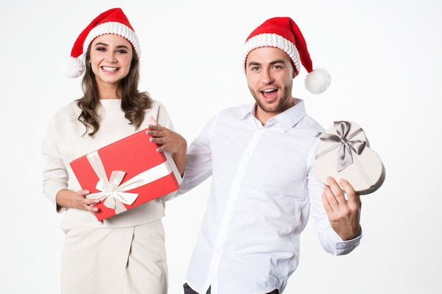 Kerstmis genieten van jong koppel met geschenken in hand op witte achtergrond.