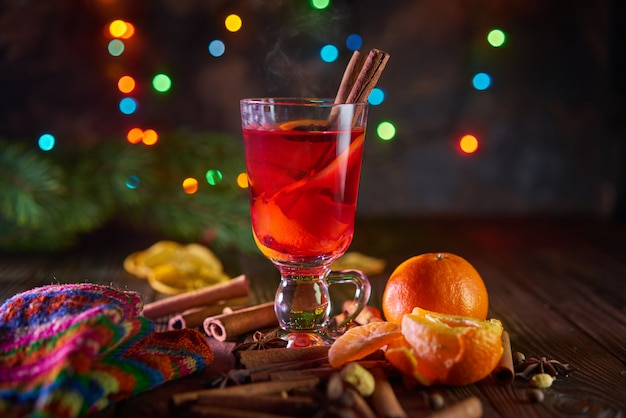 Kerstmis glühwein met sinaasappels en kruiden met bokeh lichten