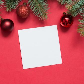 Kerstmis groenblijvende takken en rode ballen op rood.