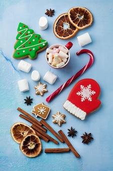 Kerstmis. groep peperkoek, kaneel, sinaasappel, speelgoed en kop warme chocolademelk op lichtblauw.