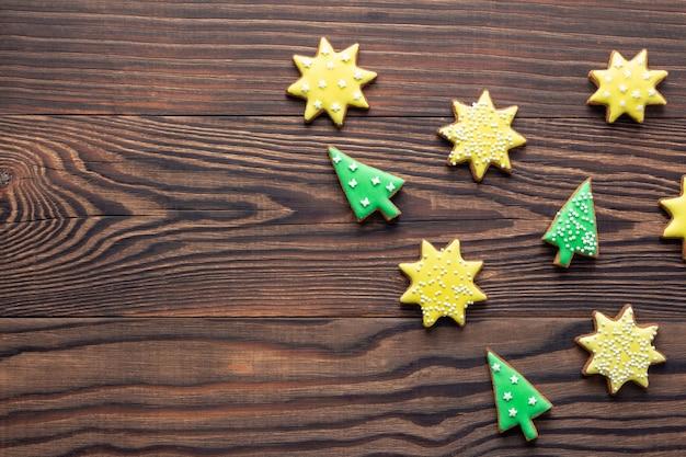 Kerstmis houten achtergrond met koekjes of peperkoek in vorm van sterren en bomen met suikerglazuur