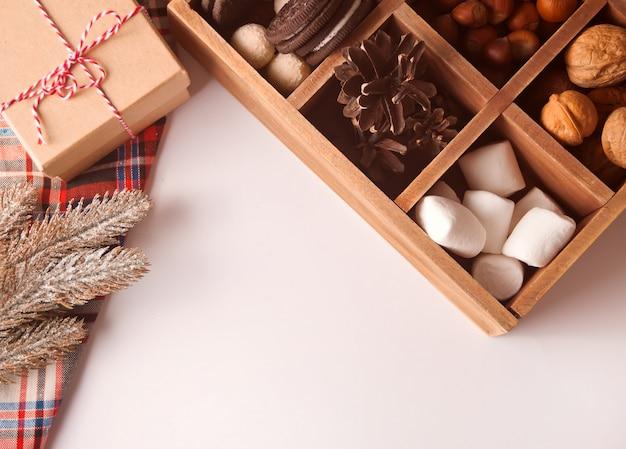 Kerstmis houten doos met marshmallows, koekjes, noten en geschenkdoos met pijnboomtak in de buurt