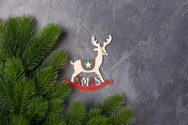 Kerstmis houten stuk speelgoed hertendecor op donkere achtergrond met bont. nieuwjaar x-mas concept. gratis exemplaarruimte. flatlay.