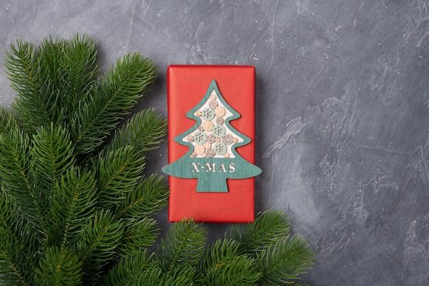 Kerstmis huidige rode doos met houten boomdecor op donkere achtergrond met bont. nieuwjaar x-mas concept. vrije ruimte.