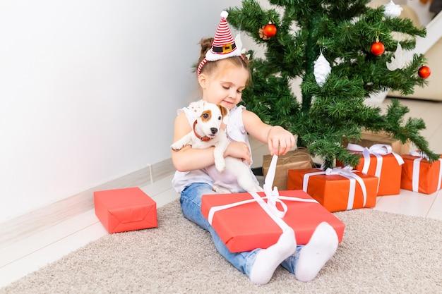 Kerstmis, huisdieren en vakantieconcept - kind in santahoed met een jack russell terrier-puppy.