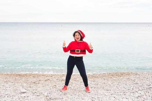 Kerstmis, humor en mensen concept - jonge gelukkige vrouw in santa claus pak op het strand duimen opdagen in de buurt van de zee.