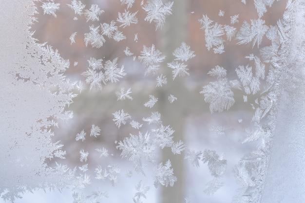 Kerstmis. ijzig patroon in de vorm van sneeuwvlokken van verschillende vormen op het vensterglas.