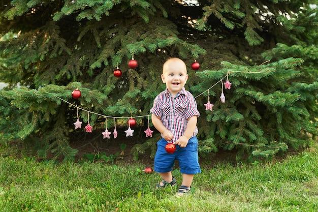 Kerstmis in juli, babyjongen met kerstmis. schieten in de zomer in het park, nieuwjaarsdecor