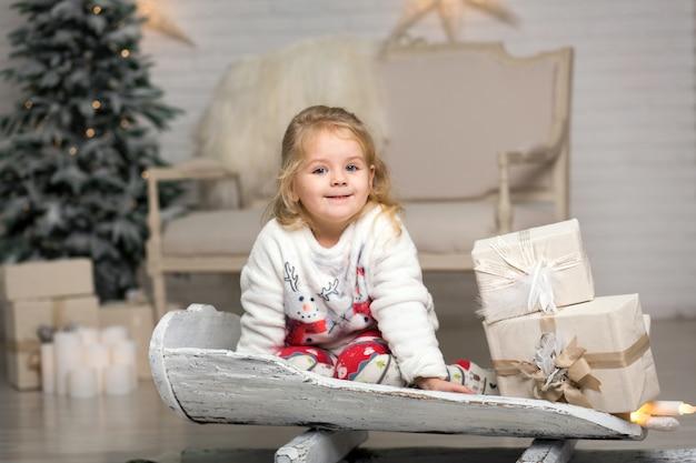 Kerstmis is er al. meisje rodelen met kerstcadeau doos. klein schattig meisje ontving vakantiegiften. kid hold geschenkdoos tijdens het rodelen. kerstmis vieren. winter activiteit