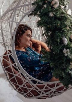 Kerstmis jong meisje gezond kapsel elegante dame houdt een tak van sparren in zijn handen