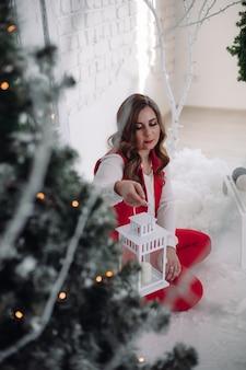 Kerstmis. jong meisje. verzinnen. gezonde haarstijl. elegante dame naast de kerstboom gelukkig nieuwjaar.