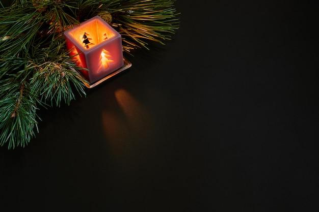 Kerstmis, kerstboom, kaars, kegels en kaneelstokjes op zwarte achtergrond. bovenaanzicht. ruimte kopiëren. stilleven. plat leggen. nieuwjaar