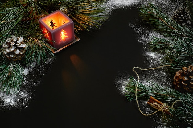 Kerstmis, kerstboom, kaars, sneeuw, kegels en kaneelstokjes op zwarte achtergrond. bovenaanzicht. ruimte kopiëren. stilleven. plat leggen nieuwjaar