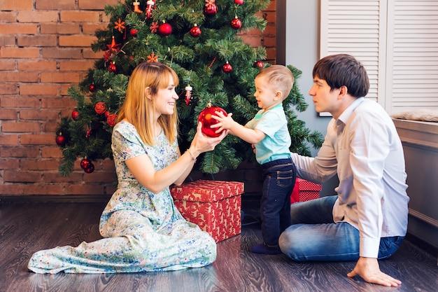 Kerstmis, kerstmis, familie, mensen, geluksconcept - gelukkige ouders spelen met schattige babyjongen