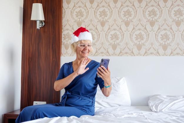 Kerstmis, kerstmis, online groetenconcept - een vrouw in een helperhoed van de kerstman met een smartphone.