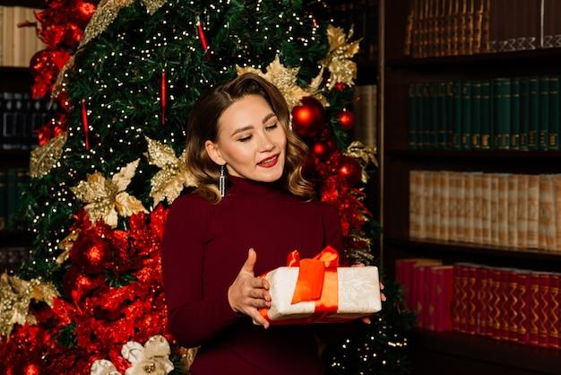 Kerstmis, kerstmis, winter, geluksconcept - glimlachende vrouw in santakleren met vele giftdozen