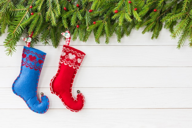 Kerstmis. kerstmisspar met decoratie, twee kerstmissokken op witte houten raadsachtergrond. copyspace