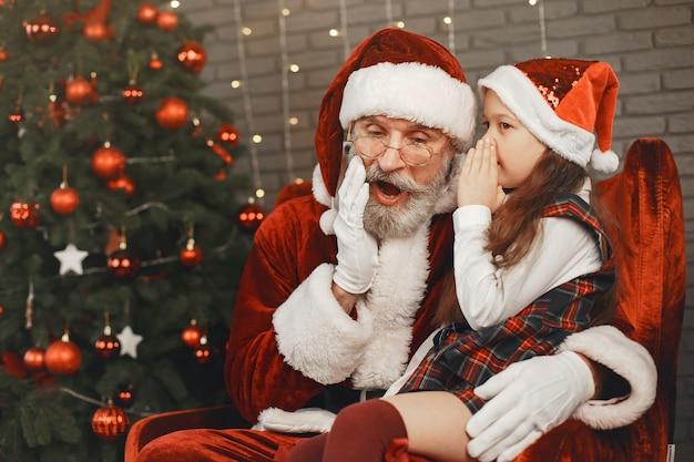 Kerstmis, kind en geschenken. de kerstman bracht cadeautjes voor het kind. blij meisje dat kerstman koestert.