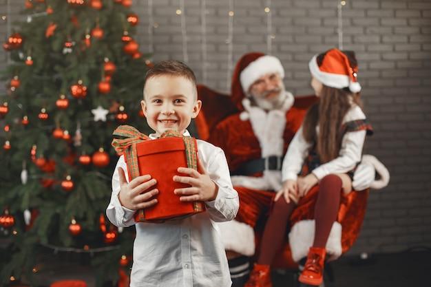 Kerstmis, kinderen en cadeaus. de kerstman bracht cadeautjes voor kinderen. vrolijke kinderen met geschenken die santa knuffelen.