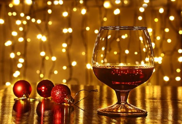 Kerstmis kleurrijke ballen en glas cognac of whisky met intreepupil lichten