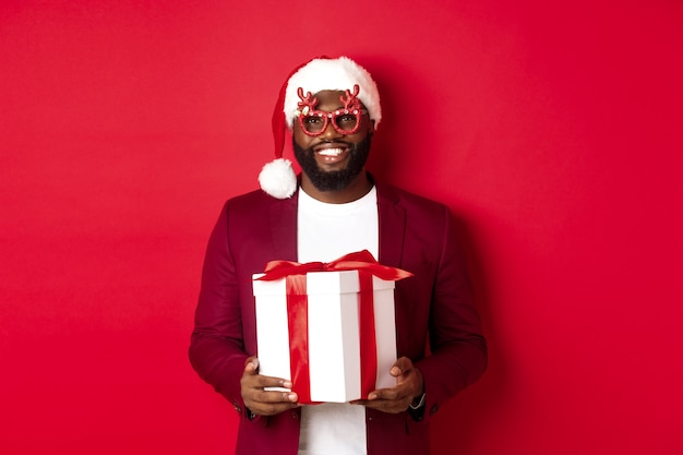 Kerstmis. knappe afro-amerikaanse man in feestbril en kerstmuts met nieuwjaarscadeau, cadeau in doos brengen en glimlachen, staande over rode achtergrond