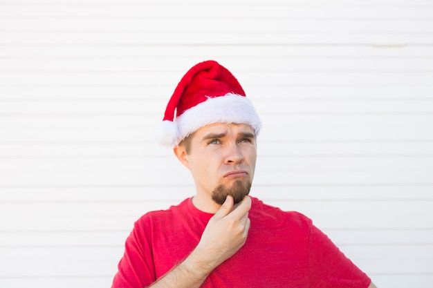 Kerstmis, mensen, emoties concept - ontevreden santa in kerstmuts wordt opgezocht