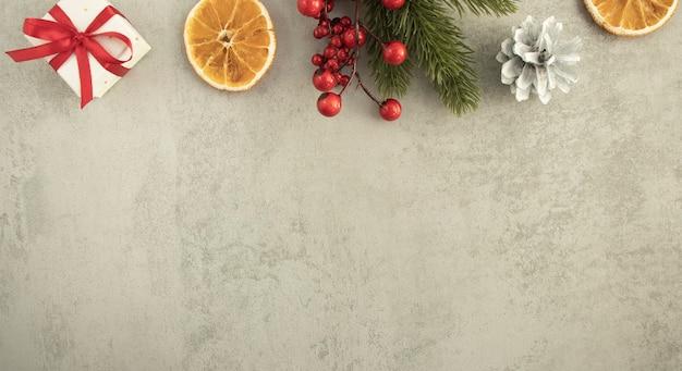Kerstmis met geschenkdoos en decoraties op grijze houten tafel.