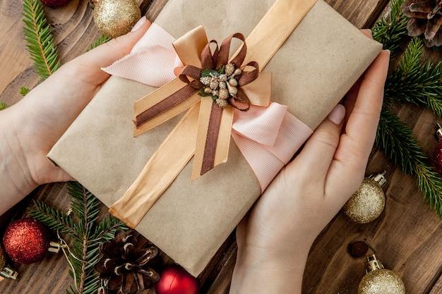 Kerstmis met geschenkdozen, papierrollen en decoraties op rood. voorbereiding op vakantie. bovenaanzicht met copyspace. vrouw handen met geschenkdoos