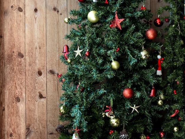 Kerstmis met ornamenten, sterren, rode en gouden bal, dennenappel en klok die op groene kerstboom op lege houten plankraad met exemplaarruimte hangen.