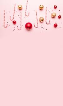 Kerstmis met snoep stokken, gouden en rode ballen op roze achtergrond. plat lag, bovenaanzicht, copyspace