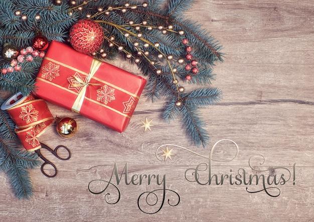 Kerstmis met versierde fir twijgen en geschenkdoos, tekst