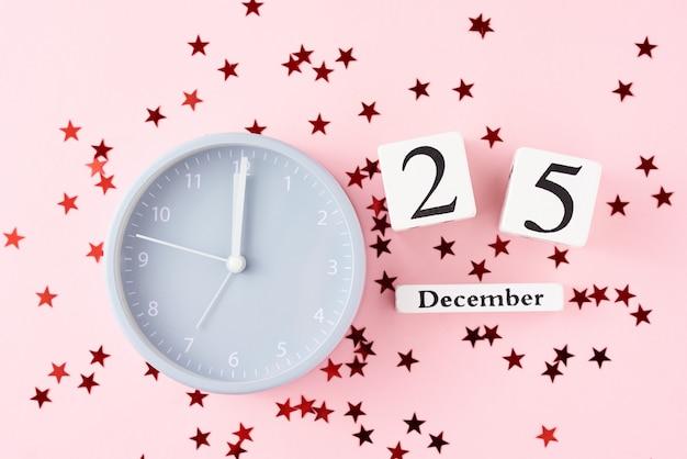 Kerstmis met wekker en sterrenconfettien op roze