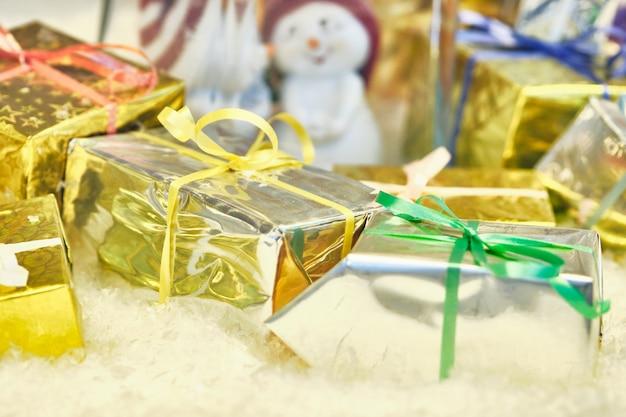 Kerstmis miniatuurdozen met giften in abstracte sneeuw.