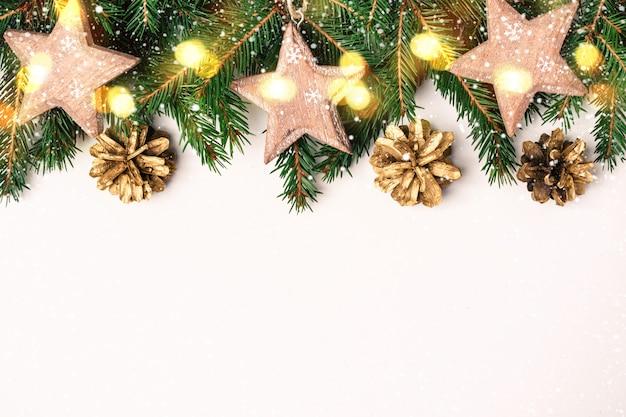Kerstmis natuur grens van dennentakken, houten ster speelgoed en bokeh lichten
