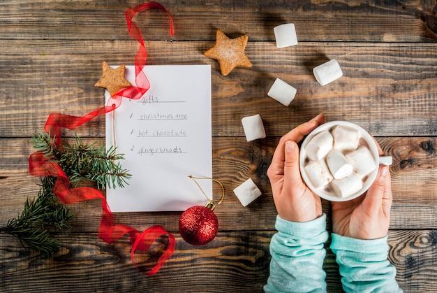 Kerstmis, nieuwjaar concept. houten tafel, notitieboekje met takenlijst, meisjeshanden houdt cacaomok, kerstbal, pijnboom, rood lint, marshmallow. bovenaanzicht copyspace