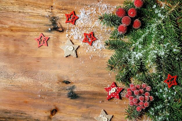 Kerstmis-nieuwjaar creatieve lay-out of wenskaart met fir tree takken, rode bessen en sterren op houten achtergrond. plat leggen, kopie ruimte