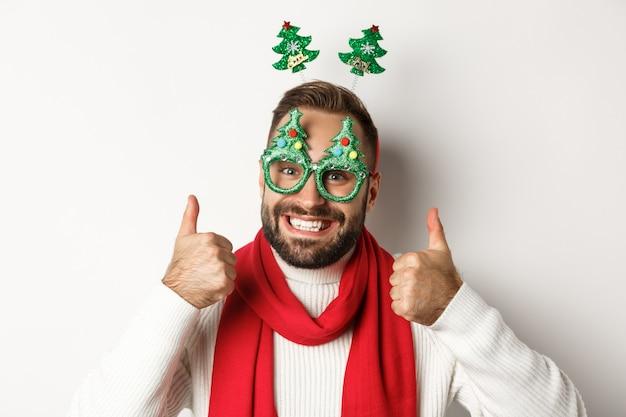 Kerstmis, nieuwjaar en viering concept. close-up van een knappe bebaarde man met een grappige feestbril die er gelukkig uitziet, duim omhoog in goedkeuring, zoals iets, witte achtergrond