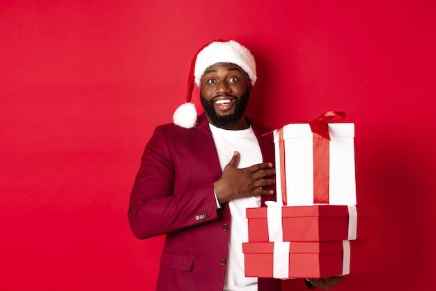 Kerstmis, nieuwjaar en winkelconcept. gelukkige zwarte man die kerstcadeaus ontvangt, bedankt zegt en dankbaar glimlacht, staande in kerstmuts tegen rode achtergrond