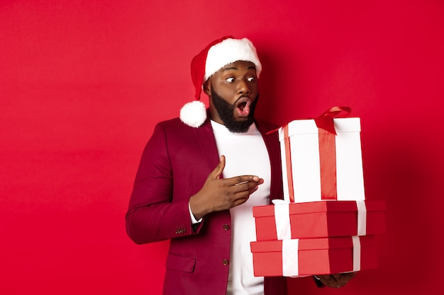 Kerstmis, nieuwjaar en winkelconcept. verrast zwarte man die met verbazing naar kerstcadeaus kijkt, een kerstmuts draagt, met geschenken tegen een rode achtergrond staat