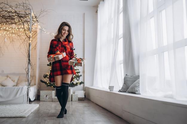 Kerstmis, nieuwjaar. mooie vrouw in overhemd en sokken die thuis met de doos van de kerstmisgift lopen