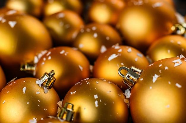 Kerstmis, nieuwjaarachtergrond. gouden kerstballen op donkere achtergrond, witte sneeuwvlokken.