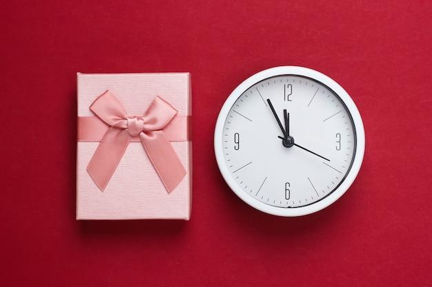 Kerstmis, nieuwjaarsthema. geschenkdoos met klok op een rode achtergrond. bovenaanzicht