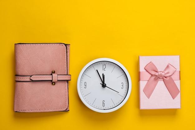 Kerstmis, nieuwjaarsthema. geschenkdoos met klok, portemonnee op geel oppervlak. bovenaanzicht