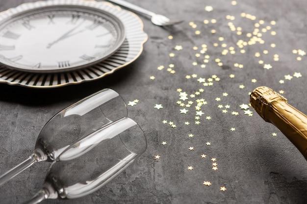 Kerstmis, nieuwjaarsvierende klokvormige schotel, champagneflessen, twee champagneglazen en gouden glitter confetti, t
