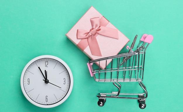 Kerstmis, nieuwjaarswinkelen. minisupermarktkarretje met giftdoos en klok op muntgroene achtergrond. bovenaanzicht