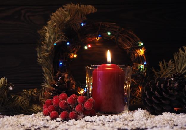 Kerstmis of advent achtergrond met een brandende kaars op sneeuw, versierd met dennentakken en ornamenten