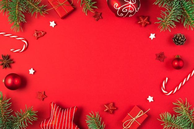 Kerstmis of gelukkig nieuwjaar achtergrond gemaakt van fir takken, dennenappels, decoraties op rode achtergrond