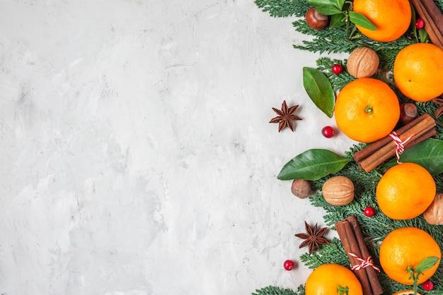 Kerstmis of gelukkig nieuwjaar achtergrond gemaakt van fir tree takken, mandarijnen, noten en bessen op concrete achtergrond. plat leggen. bovenaanzicht met kopie ruimte