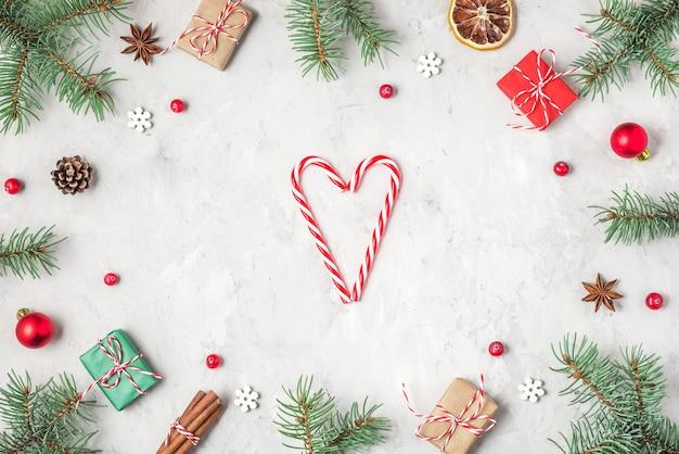 Kerstmis of gelukkig nieuwjaar samenstelling. frame gemaakt van sparren takken, decoraties voor de feestdagen en geschenkdozen en hart op betonnen ondergrond. plat liggen. bovenaanzicht met kopieerruimte